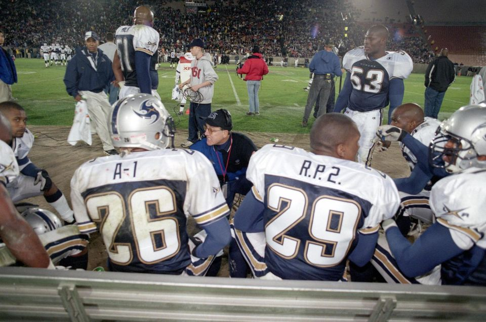Head Coach Al Luginbill of the Los Angeles Xtreme discusses strategy with Dell 'A-1' McGee #26 and Ricky 'R.P. 2' Parker #29 during an XFL game against the Chicago Enforcers at the L.A. Coliseum in Los Angeles, California.