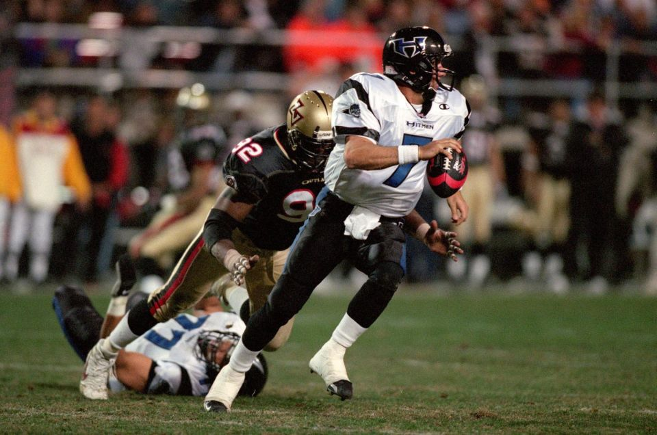 Charles Puleri #7 of the New York/New Jersey Hitmen moves with the ball away from Kelvin Kinney #92 of the Las Vegas Outlaws during an XFL game at the Sam Boyd Stadium in Las Vegas, Nevada.