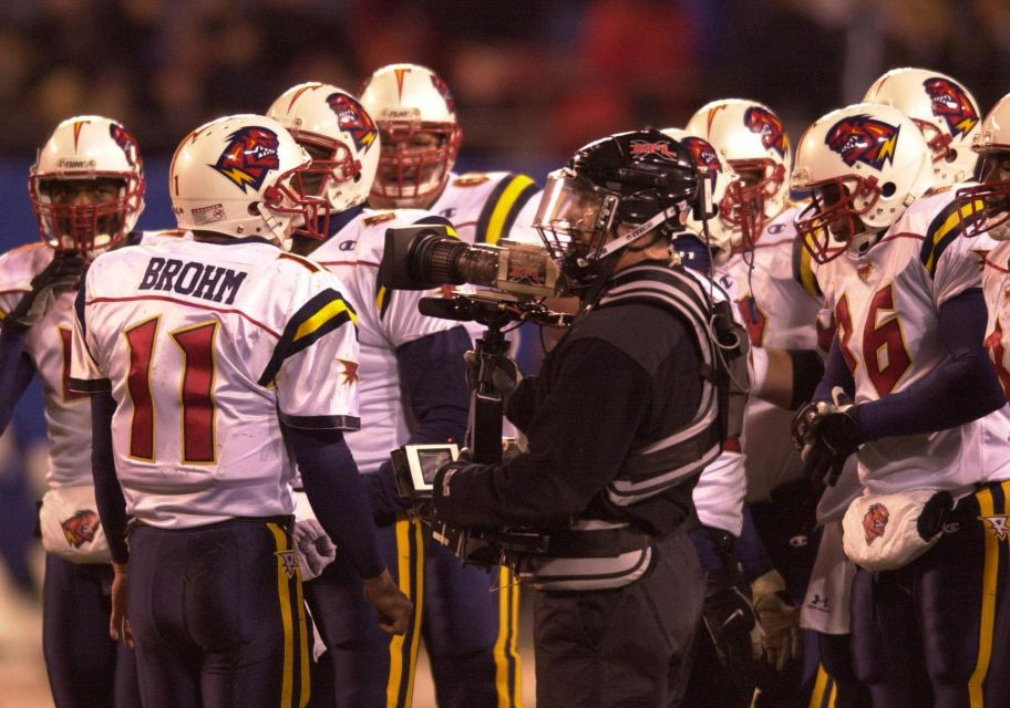 An XFL cameraman in the huddle of the Orlando Rage during their game against the New York Hitmen at Giant Stadium in East Rutherford, New Jersey.