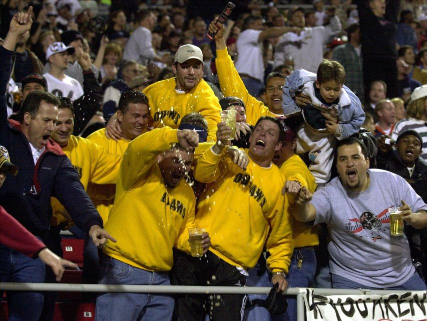 Las Vegas Outlaws fans spill their beer as they cheer during the first half of the XFL game against the New York/New Jersey Hitmen at Sam Boyd Stadium in Las Vegas on Saturday, Feb. 3, 2001.