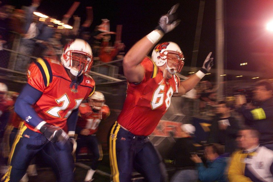 Michael Black #21 and Dan Goodspeed of the Orlando Rage run on to the field before they take on the Chicago Enforcers during XFL opening night at the Citrus Bowl in Orlando, Florida.