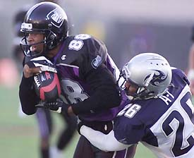 Junior Lord of the Chicago Enforcers is dragged down by Dell McGee of the Los Angeles Xtreme in the second half. (Allsport)